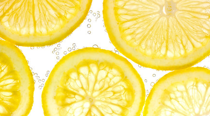Slices of lemon in water with air bubbles