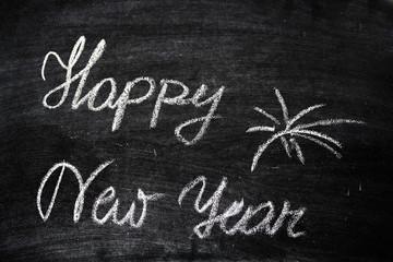 Happy New Year Slogan Written On A Black Chalkboard