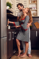 Picture of happy loving woman and man preparing food in kitchen