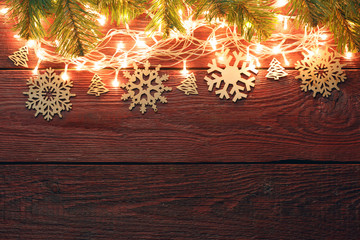 Picture of New Year's wooden red background with burning garland from above, snowflakes.