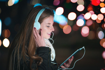 Woman with headphones using tablet and listening music in city at night