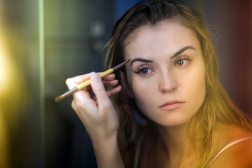 Sleppy woman putting morning makeup in bathroom, authentic portrait