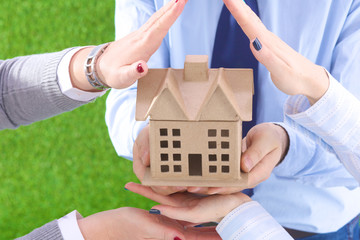 The house is in the hands of men and women on a grass background