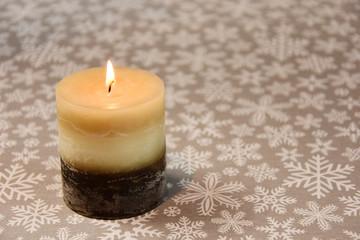 Dekoracja świąteczna, płonąca świeczka na gwiaździstym tle.