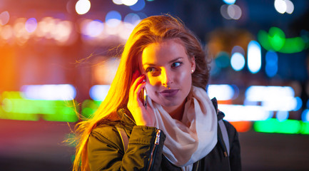 Woman using mobile phone at night in the city among neon lights