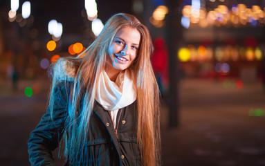 Beautiful girl walking in the city at night