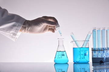Hand of laboratory worker and chemical glassware