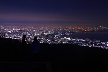 Young couple looking at the night city lights