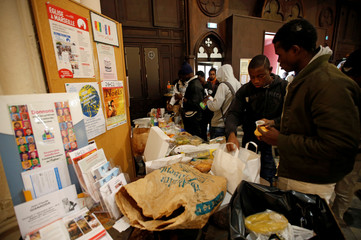 Volonteers of associations distribute foods to migrants as they occupy the Saint Ferreol church to protest against the life conditions of unaccompanied minor migrants in Marseille
