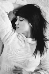 Brunette calm young woman lying on bed or carpet in white knitted sweater. Monochrome