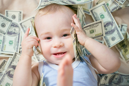 Cute hapy baby boy playing with a lot of money, american hundred dollars cash