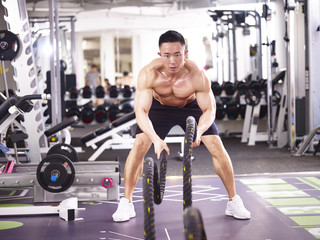 asian bodybuilder exercising with battle rope in gym