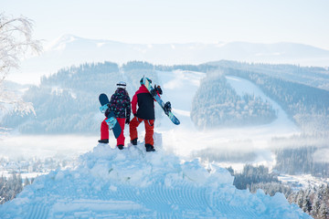 Couple of snowboarders enjoy the snow-white scenery of mountains and forests of the Carpathians from the height of the mountain top at winter ski resort on a beautiful sunny day. Back view