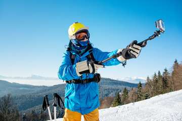 Skier in colorful winter clothing taking a selfie with action camera on selfie stick posing on top of a mountain