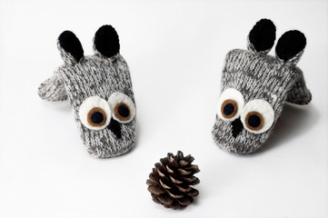Christmas composition. Woolen knitted mittens in dogs with pine cone. isolated white.
