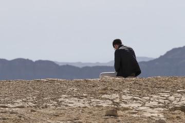 Rear view of man sitting on rock, Makhtesh Ramon, Negev Desert, Israel