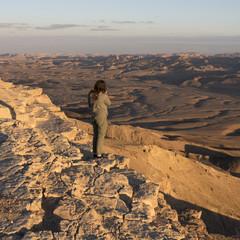 View of teenage girl standing on rock in desert, Makhtesh Ramon, Negev Desert, Israel