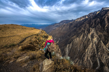 Young woman meditate above the deepest canyon Colca. Panoramic breathtaking view of peruvian village and canyon Colca , Peru, South America