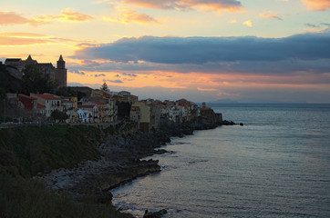 Village Cefalu houses on the cliffs and waves crashing rocks at sunset. Sicily, Italy