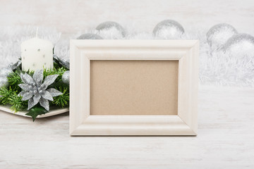 Christmas decoration with candle and empty photo frame on white wooden background. White frame mock-up.
