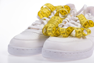 Sneakers with measuring tape on white background.