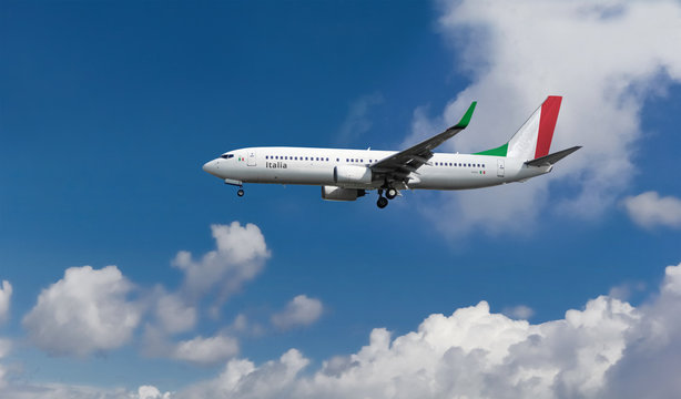 Commercial airplane with Italian flag on the tail and fuselage landing or taking off from the airport with blue cloudy sky in the background