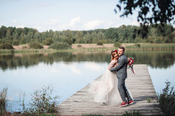 Bride and groom pose together before a beautiful lake in a sunny day