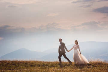 Bride and groom run on the hill before beautiful mountain landscape