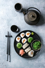 Homemade sushi rolls set with salmon, sesame seeds serving in black plate with pink pickled ginger, soy sauce, wasabi, seaweed salad, chopsticks on gray texture background. Top view, space