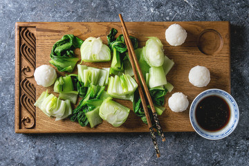 Stir fried bok choy or chinese cabbage with soy sauce and rice balls served on decorative wooden cutting board with chopsticks over gray texture background. Top view with space. Asian style dinner