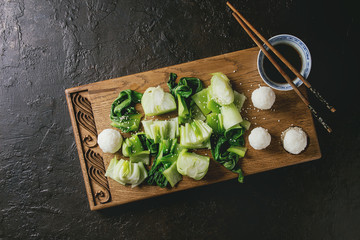 Stir fried bok choy or chinese cabbage with soy sauce and rice balls served on decorative wooden cutting board with chopsticks over dark texture background. Top view with space. Asian style dinner