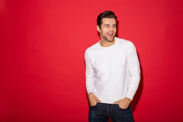 Happy man in sweater looking away with arms in pockets