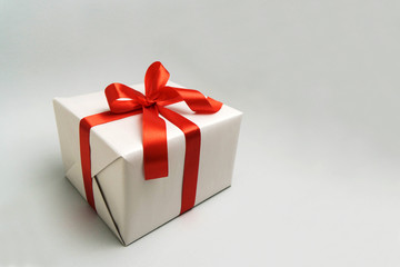 Gift box with red ribbon on it.