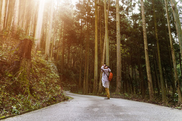 A man taking photograph in the natural park, in the morning with sun light ray