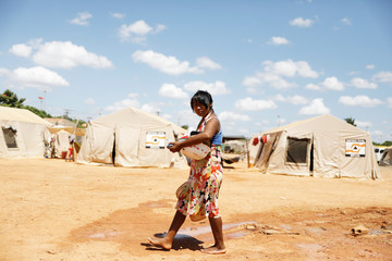An indigenous Warao woman from the Orinoco Delta in eastern Venezuela, washes clothes at a shelter in Boa Vista