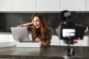 Happy young girl recording video blog episode