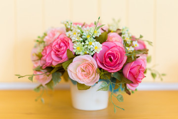Plastic colorful roses with pot on wooden table