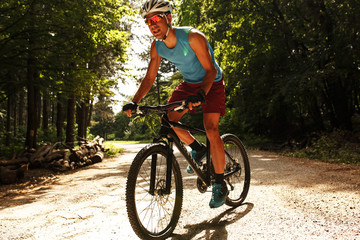 Young man riding a mountain bike on old country road.Spring season.