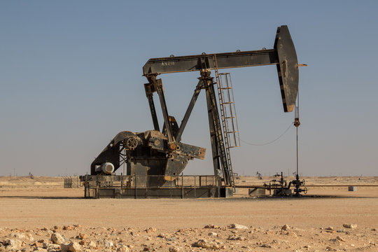 Crude oil drilling well pumping the black gold out of the soil on an oil field of the Sultanate of Oman petrol industry in the arabic middle east