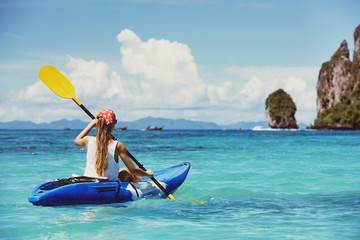 Travel concept with single girl on kayak at tropical bay