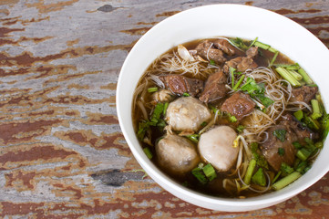 Meat Noodle. Thin rice noodle with Stewed Beef and meat ball. Top view on wooden table with copy space.