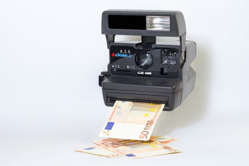 Old camera printing out cash, money earning concept