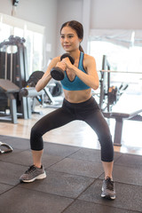 Portrait of Attractive young Asian Woman holding dumbbell in a Fitness Club.
