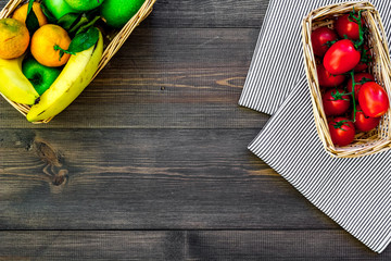 Fruits for picnic. Apple, banana, tangerine on tablecloth and dark wooden background top view copyspace