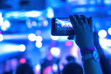 Blurred. Video recording of the concert on the smartphone phone of the Beach or club party. Conceptual background of the youth party.