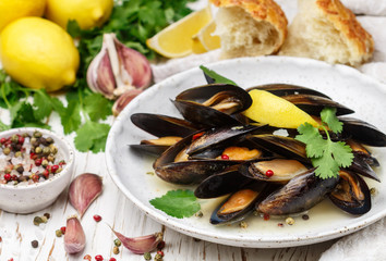 Delicious mussels in white wine with lemon, garlic, herbs and spices. Cilantro and pepper. Seafood. Clams in the shells. Snack for gourmets. Selective focus