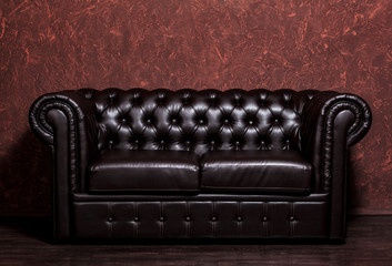 Vintage old dark brown leather sofa with grunge brown wall in the living room