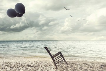 surreal image of a chair held in balance by flying balloons