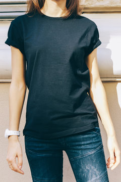 Slender woman in a black T-shirt and blue jeans
