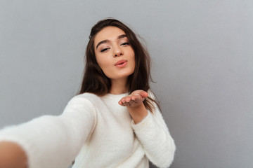 Close-up portrait of joyful brunette woman sending air kiss while taking selfie on mobile phone